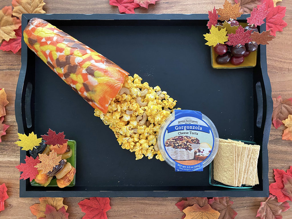 Photo of adding leaves and popcorn to fall dessert board