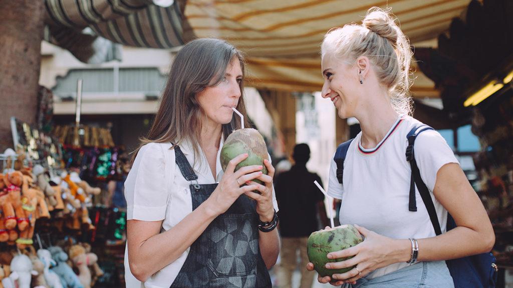 Photo of two women enjoying coconuts