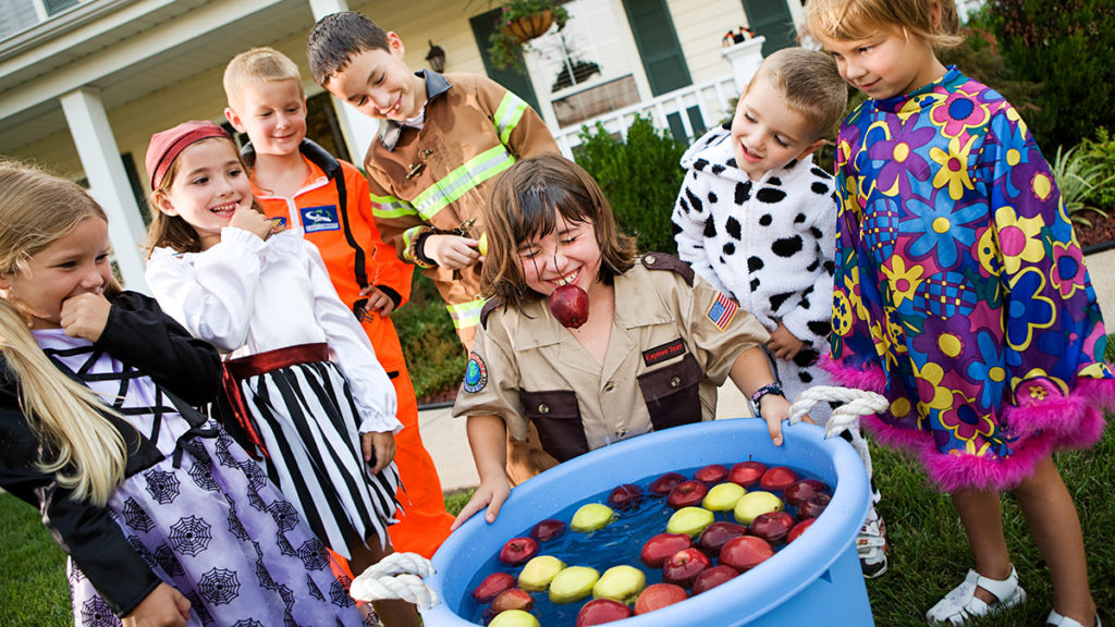Photo of kids bobbing for apples at a fall birthday party