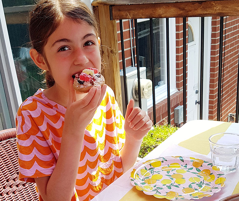 Photo of girl eating a mini chocolate chip cookie pizza