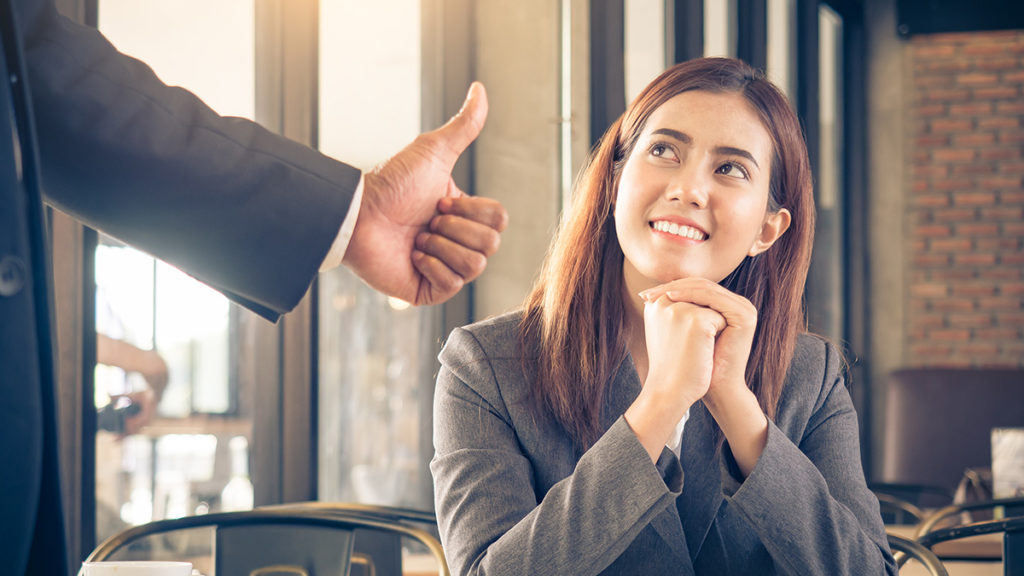 Photo of boss showing an employee appreciation by giving her a thumbs-up
