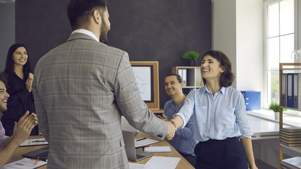 Photo of two colleagues shaking hands in a work meeting