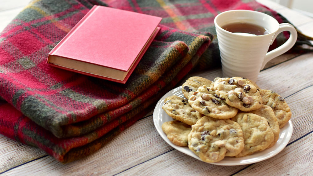 Photo of a plate of peanut butter chocolate chunk cookies with a book and a cup of tea