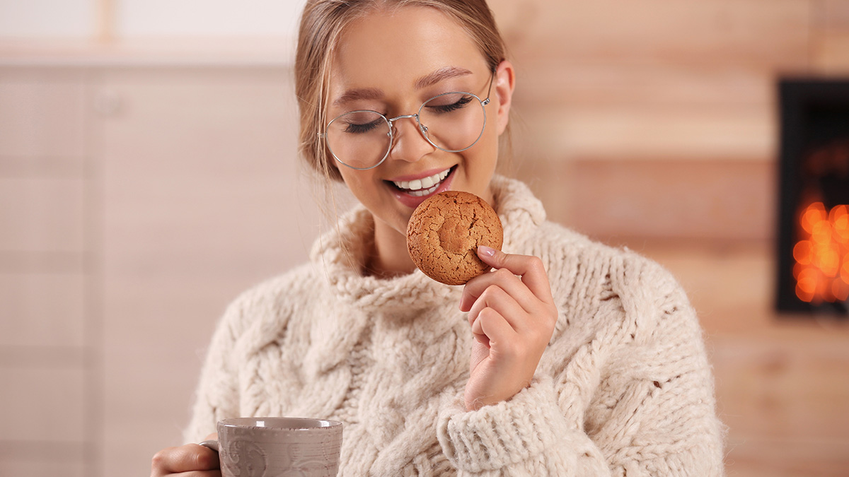 Photo of a woman enjoying a cookie and tea