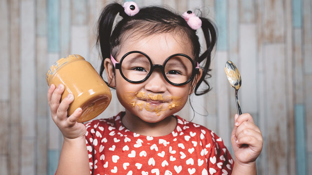 Photo of a girl eating peanut butter