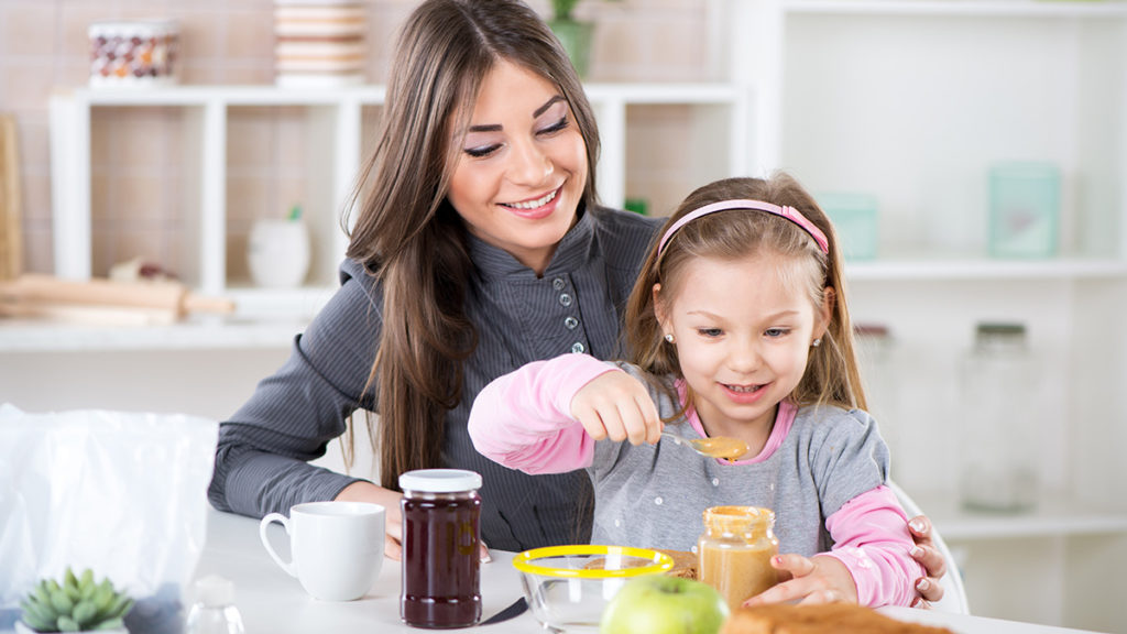Photo of mother and daughter making a peanut butter and jelly sandwich