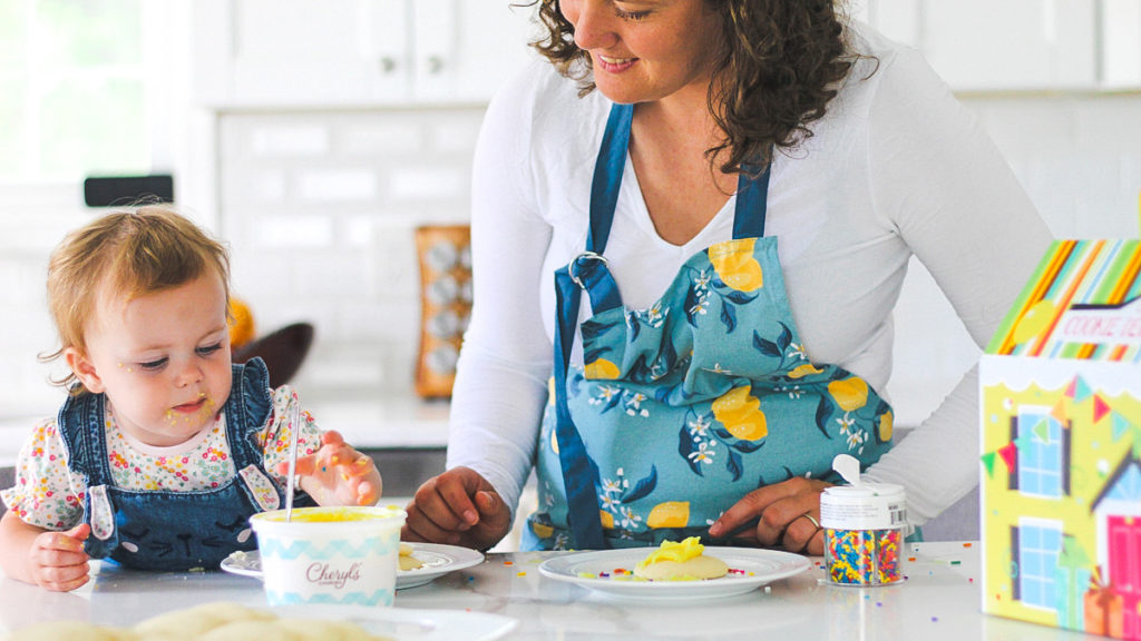 Photo of mother decorating cookies with young daughter
