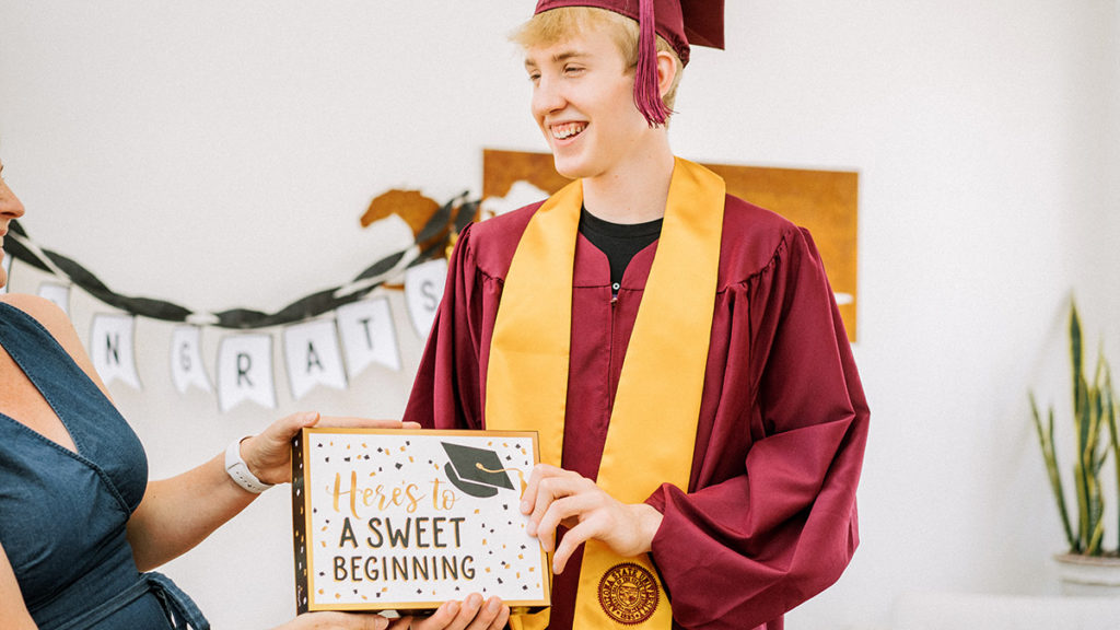 Photo of young man receiving a graduation gift from mother
