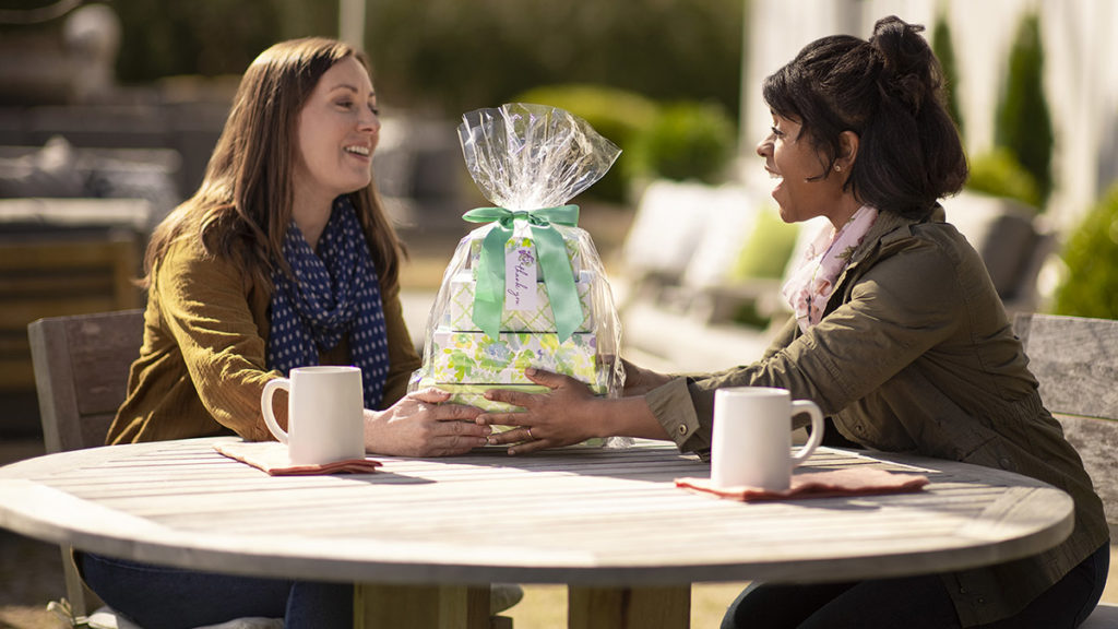 Photo of woman giving friend a gift