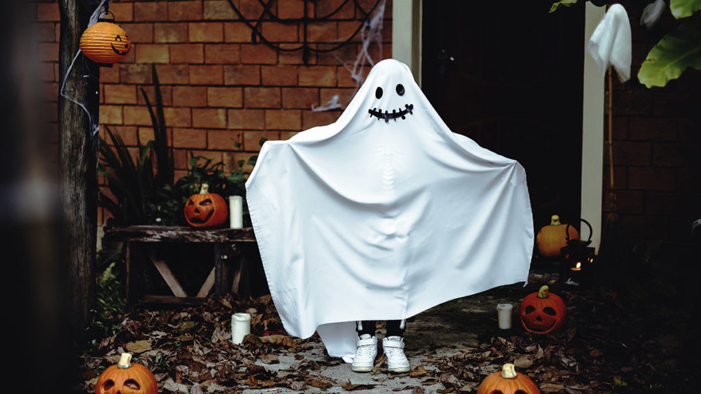 Photo of kid dressed as a ghost at front door